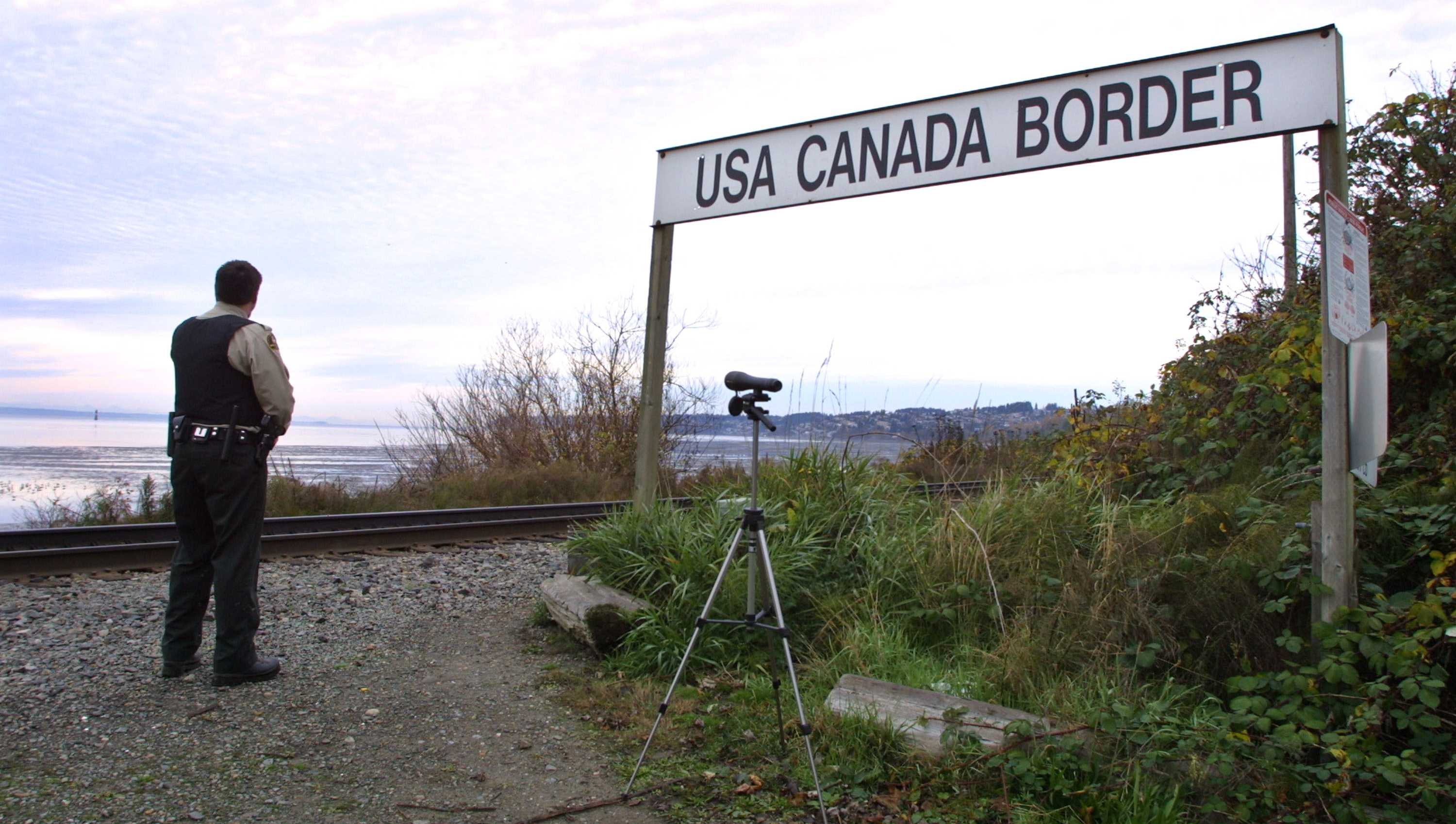 A Canadian Customs and Fisheries officer watches over the U.S.-Canada border between Blaine, Washington and White Rock, British Columbia, in White Rock, BC.