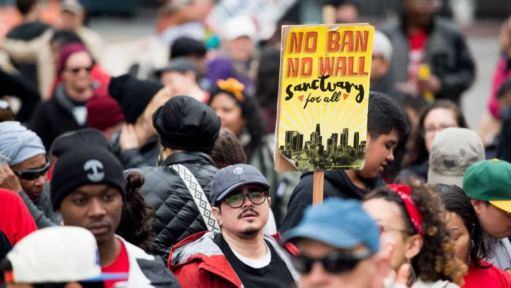 Camilo Zamora carries a sign supporting sanctuary cities during a march in Oakland, California on Jan. 15, 2018.