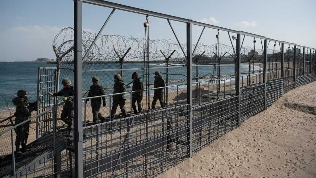 In a photo taken on Feb. 11, 2018, South Korean soldiers walk between a barbed wire fence on a beach on South Korea's northeast coast.