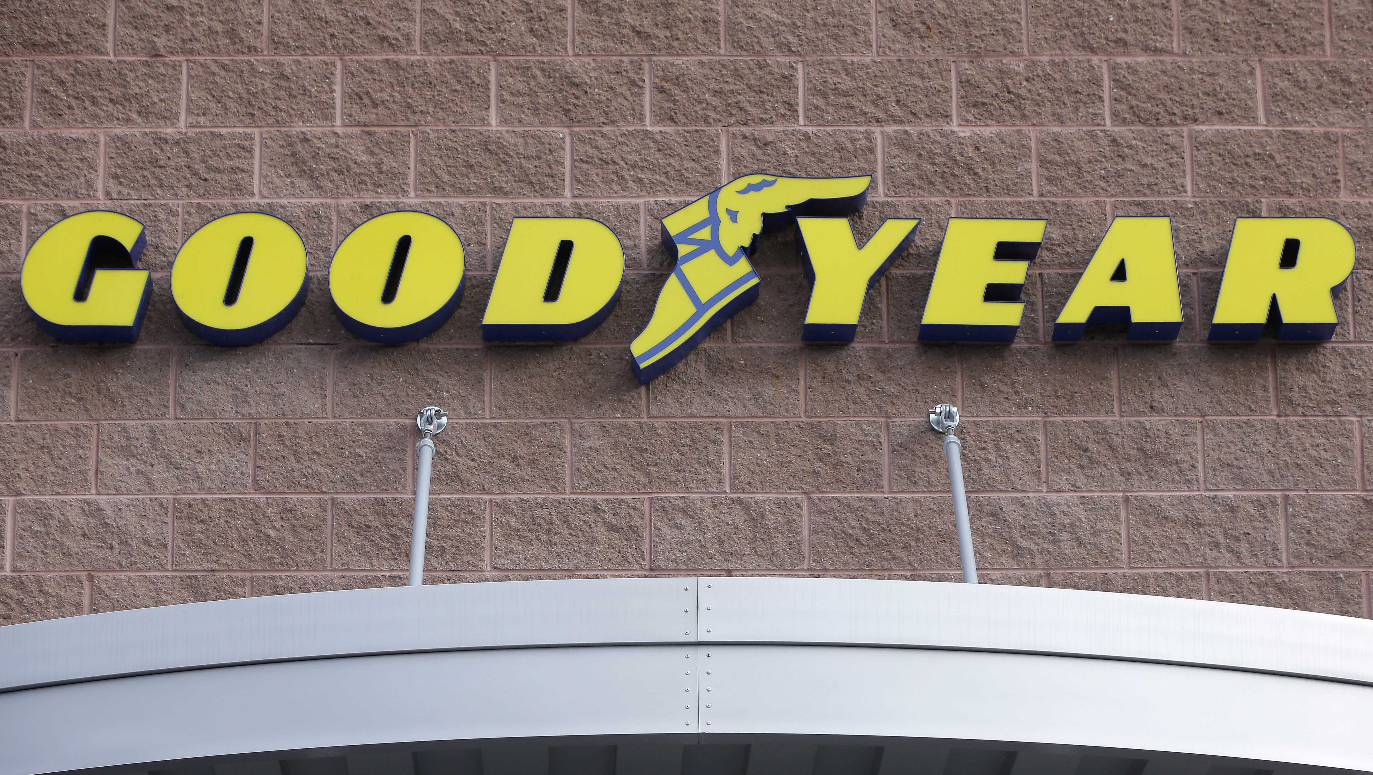 In this Nov. 30, 2017 photo a Goodyear logo is attached to the front of a Goodyear Auto Service Center, in Stoneham, Mass.