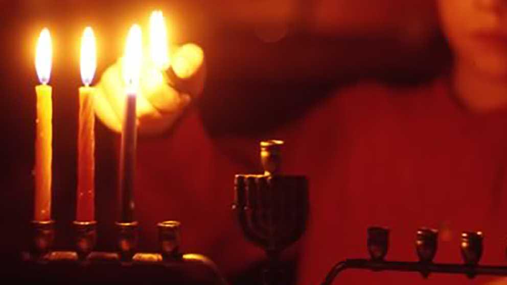 A boy lights a menorah during Hanukkah.