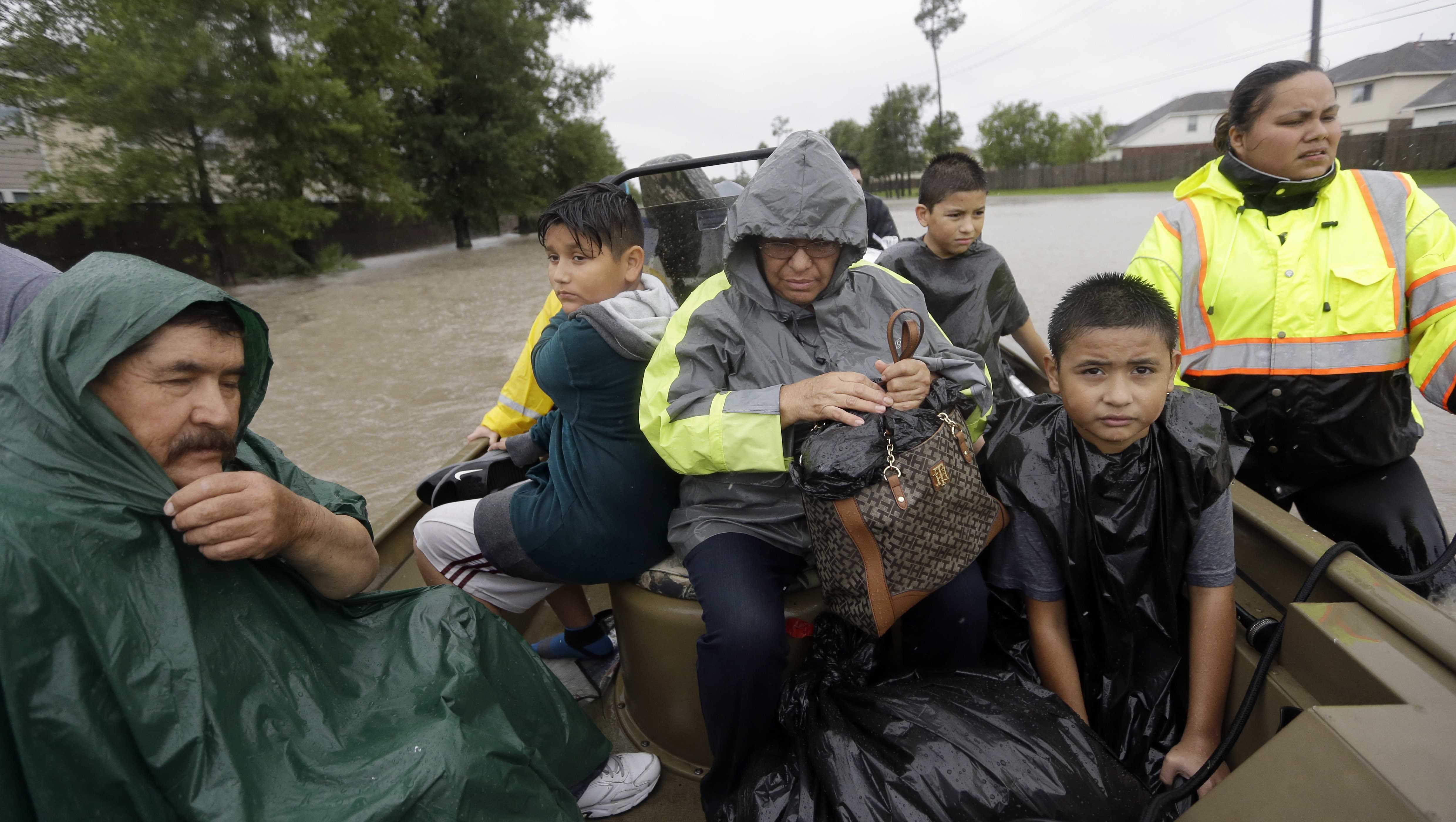 Evacuees ride in a boat down Tidwell Rd. as floodwaters from Tropical Storm Harvey rise Monday, Aug. 28, 2017, in Houston