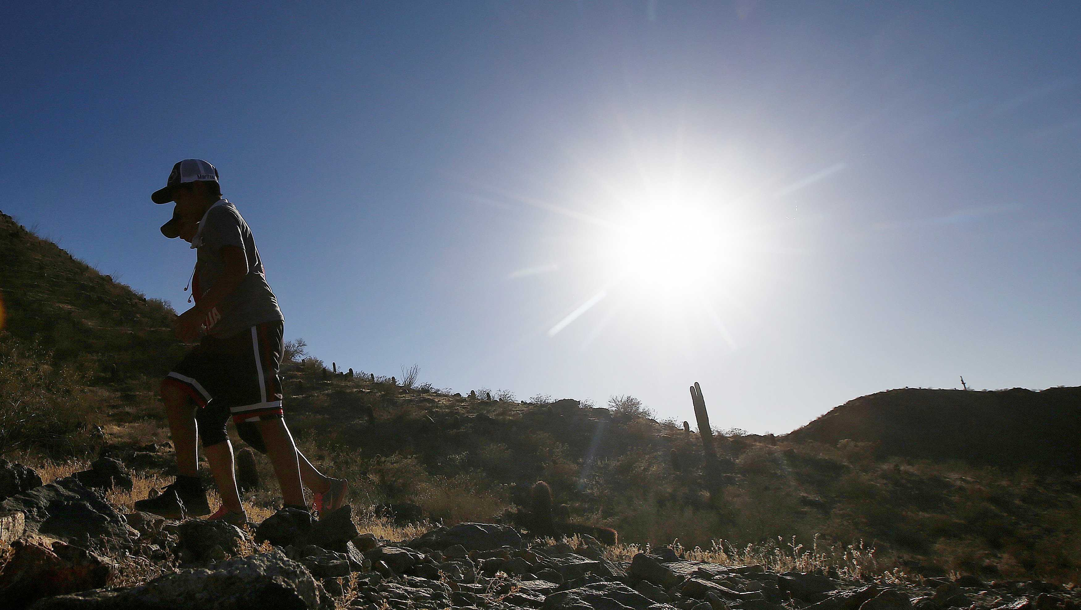 In this June 15, 2017 file photo, hikers brave the afternoon sun as the temperatures hit 110-degrees in Phoenix. Killer heat is getting worse, a new study shows.
