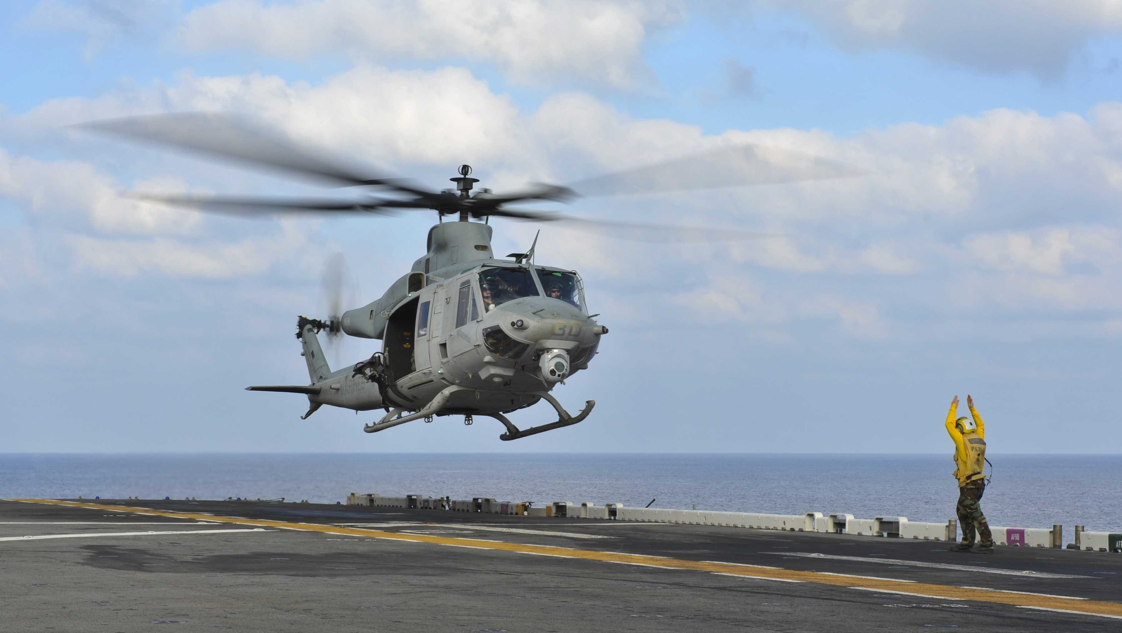An Aviation Boatswain's Mate directs a UH-1Y Venom helicopter as it lifts off from the USS Bonhomme Richard.