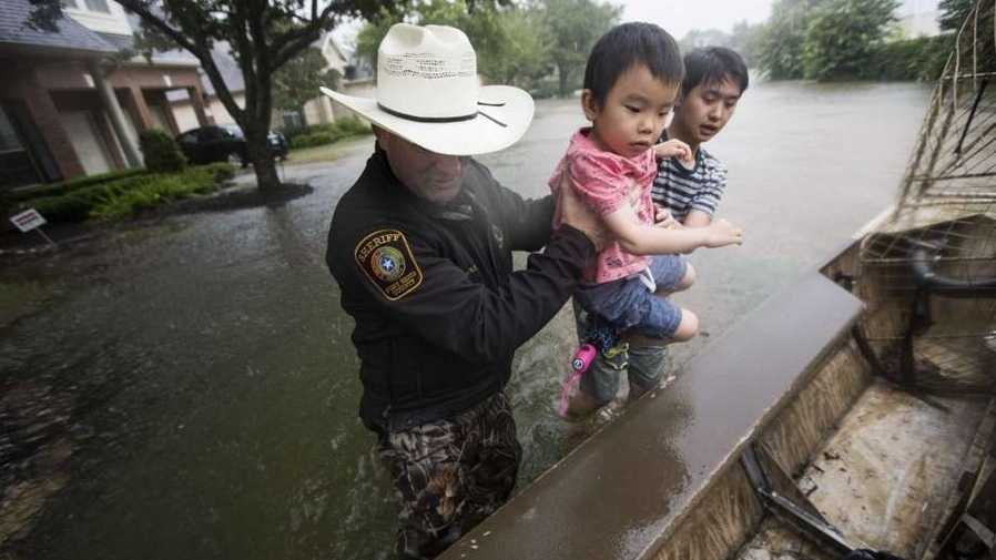 Fort Bend County Sheriff Troy Nehls and Lucas Wu lift Ethan Wu into an airboat as they are evacuated from rising waters.