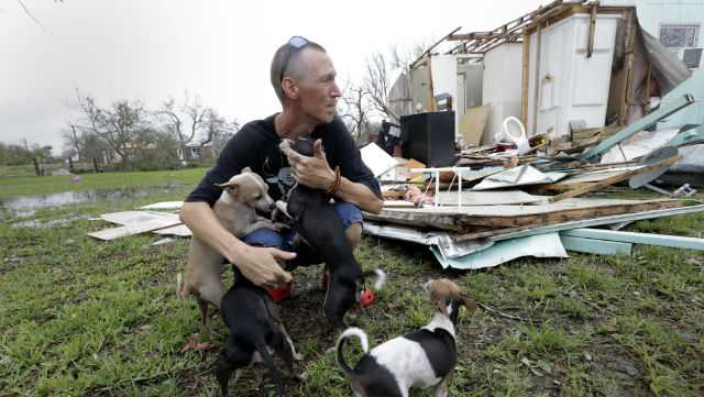 Sam Speights tries to hold back tears while holding his dogs and surveying the damage to his home in the wake of Hurricane Harvey, Sunday, Aug. 27, 2017, in Rockport, Texas. Speights tried to stay in his home during the storm but had to move to other shelter after his home lost its roof and back wall.