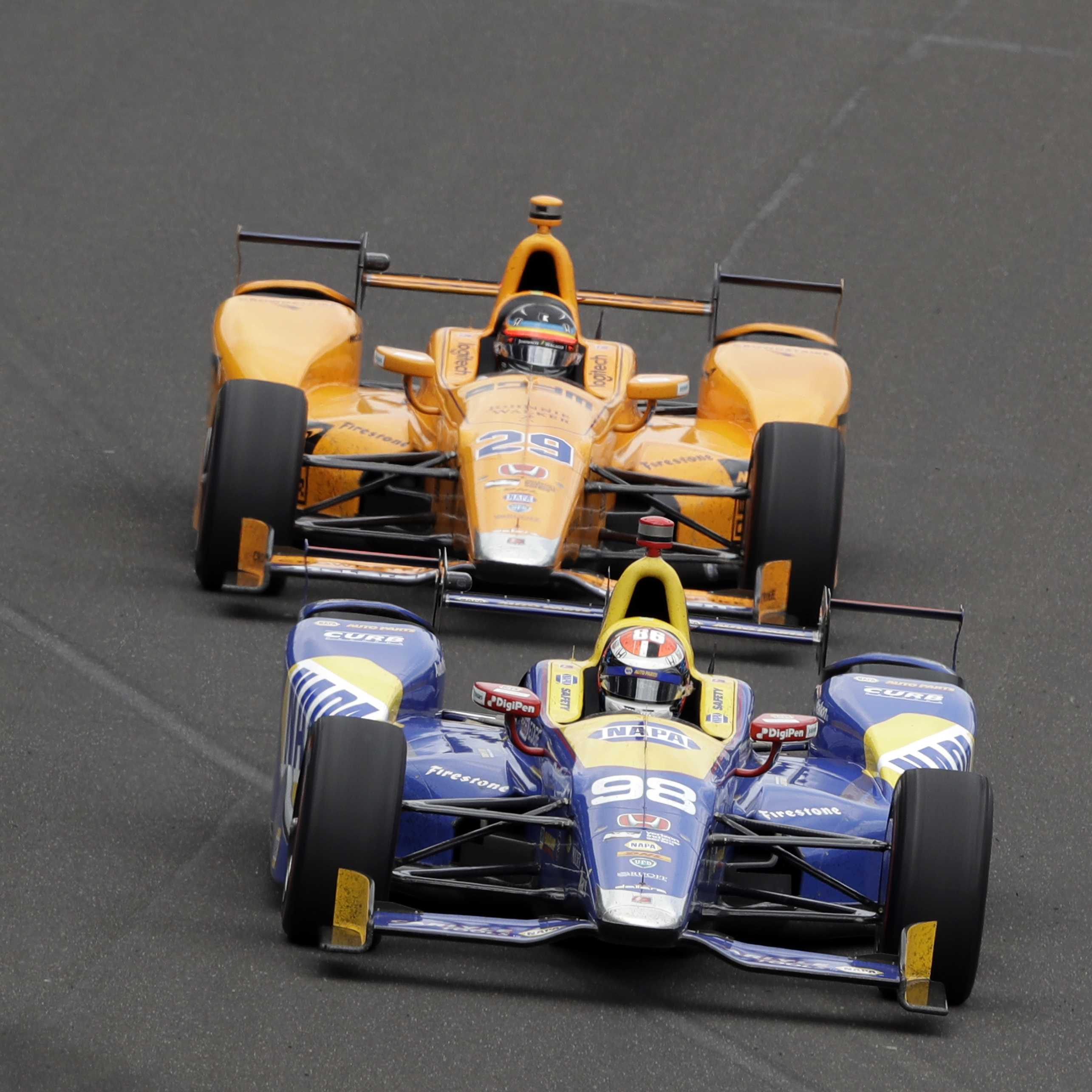 Alexander Rossi leads Fernando Alonso, of Spain, into the first turn during the running of the Indianapolis 500 auto race at Indianapolis Motor Speedway, Sunday, May 28, 2017, in Indianapolis.