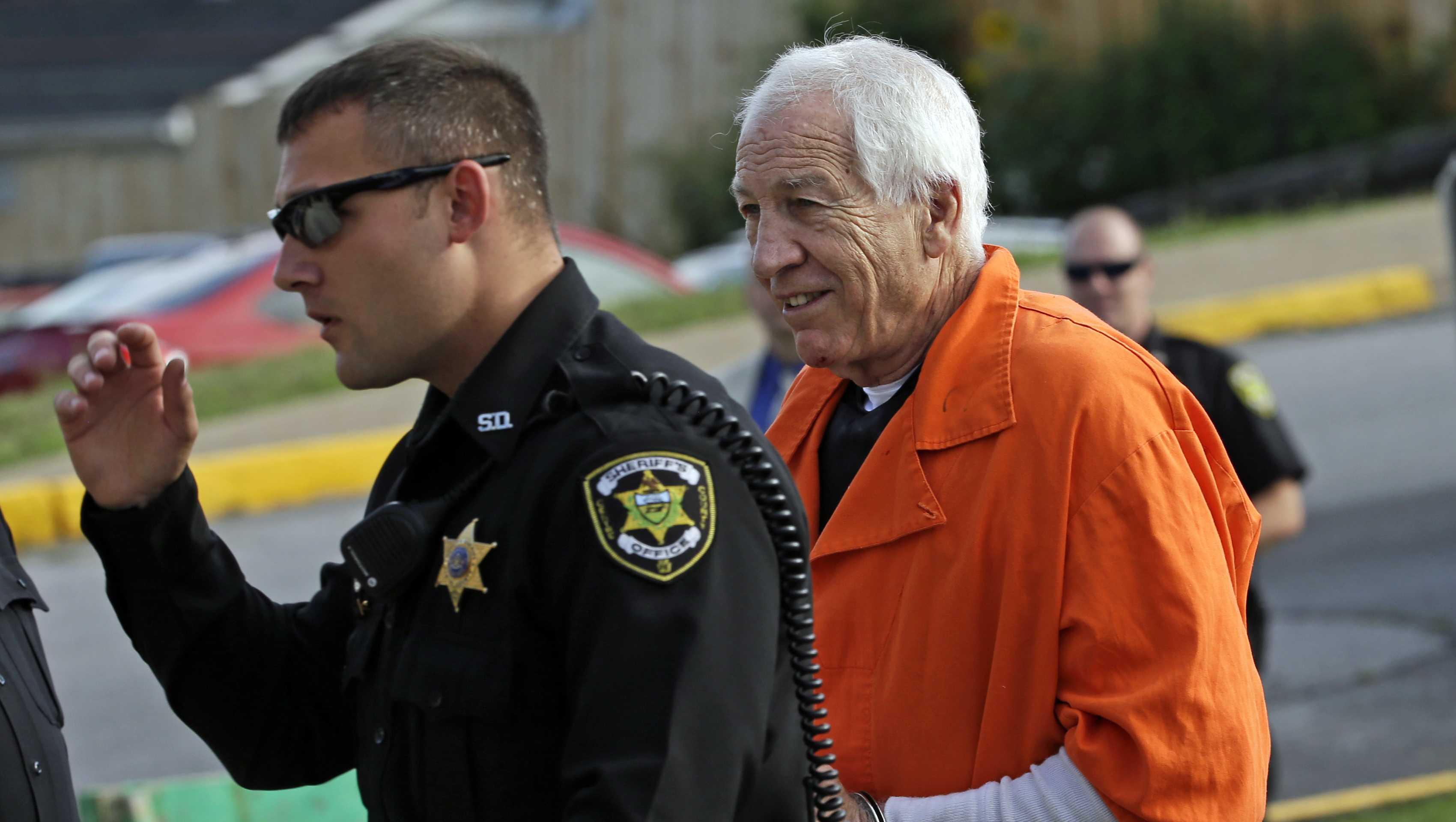 Former Penn State University assistant football coach Jerry Sandusky, right, arrives at the Centre County Courthouse.