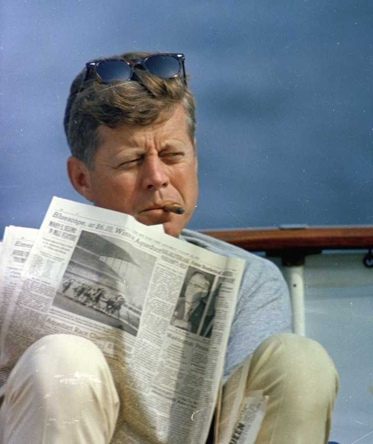 President John F. Kennedy smokes a cigar and reads the newspaper aboard the Presidential yacht Honey Fitz during Labor Day weekend off the coast of Hyannis Port, Massachusetts
