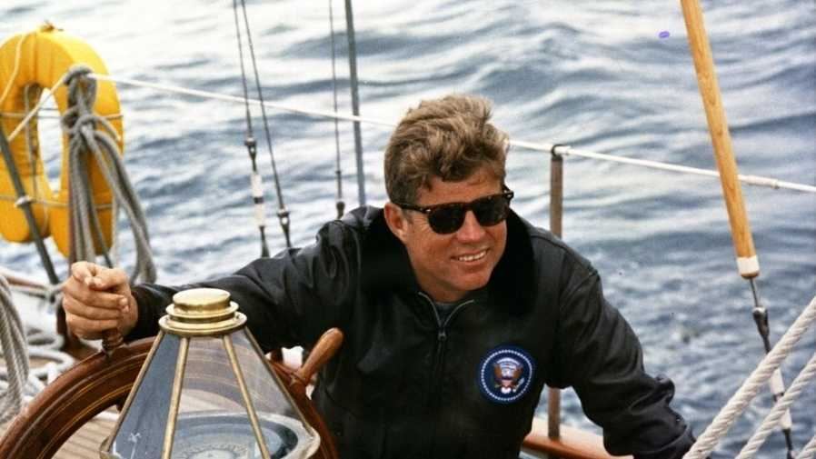 "President John F. Kennedy sits at the helm of the United States Coast Guard boat ""Manitou"" while sailing off the coast of Johns Island, Maine"