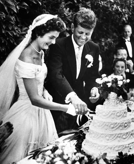 Jacqueline Bouvier Kennedy and John F. Kennedy cut their wedding cake during their reception at Hammersmith Farm. Also pictured: Ethel Skakel Kennedy. Newport, Rhode Island.