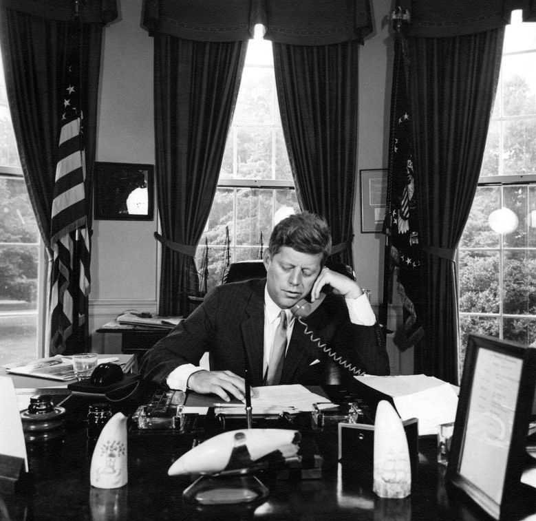 President John F. Kennedy (seated at desk) delivers remarks via telephone to the American Veterans of World War II (AMVETS) Convention in New York, New York. Oval Office, White House, Washington, D.C.