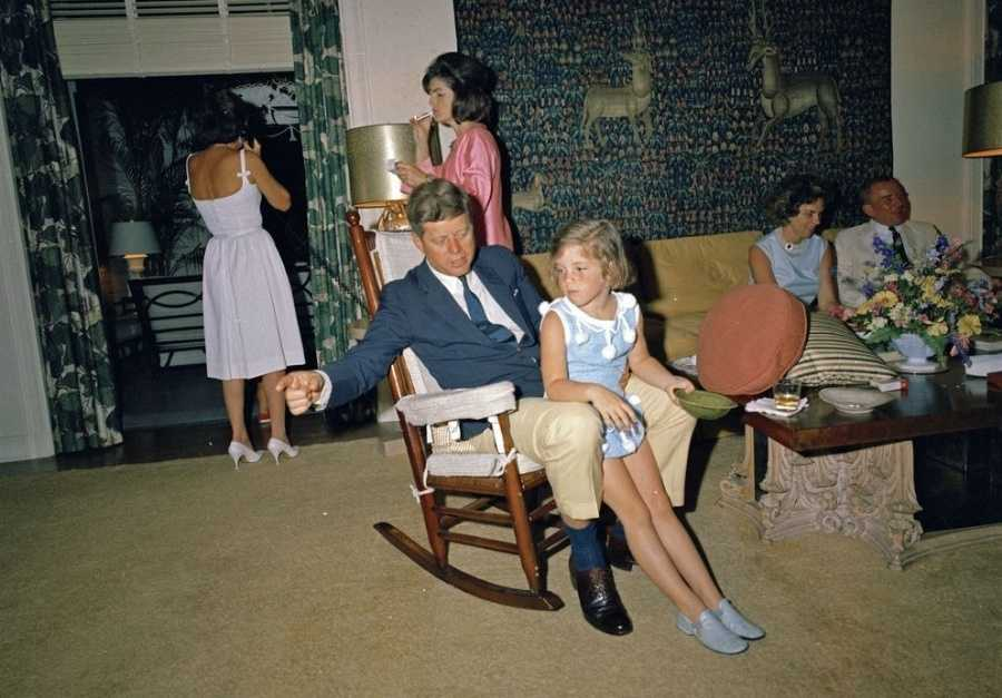 "President John F. Kennedy (in rocking chair, gesturing with right arm) visits with his daughter, Caroline Kennedy, during Easter holiday celebrations at the residence rented from Kennedy family friend C. Michael Paul in Palm Beach, Florida. First Lady Jacqueline Kennedy and an unidentified woman (speaking on telephone) stand in back&#x3B; Under Secretary of the Navy Paul ""Red"" Fay and his wife, Anita Marcus Fay, sit on the couch at right."