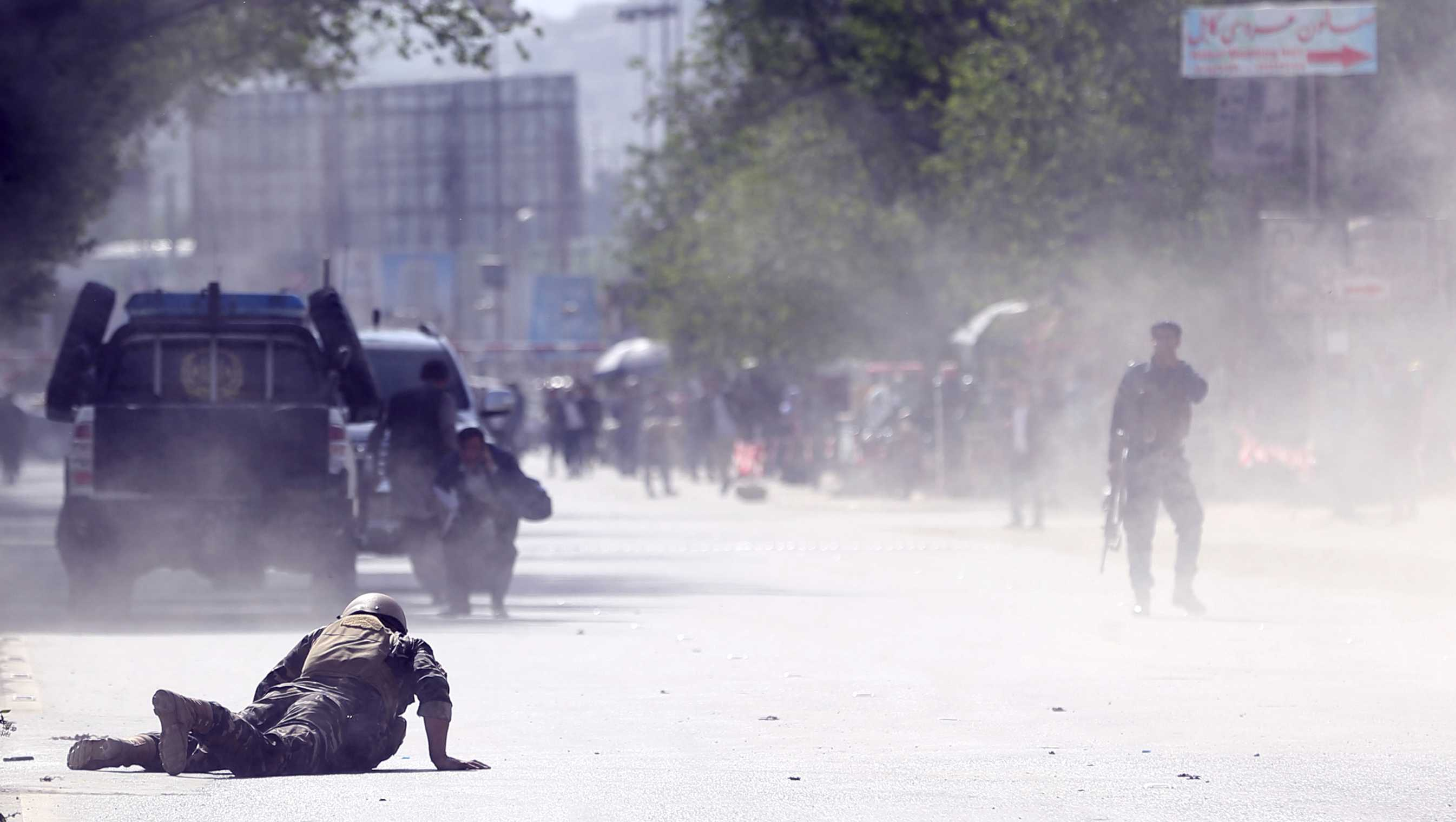 A security force and a civilian lie low at the site of a suicide attack after the second bombing in Kabul, Afghanistan, Monday, April 30, 2018. A coordinated double suicide bombing hit central Kabul on Monday morning.