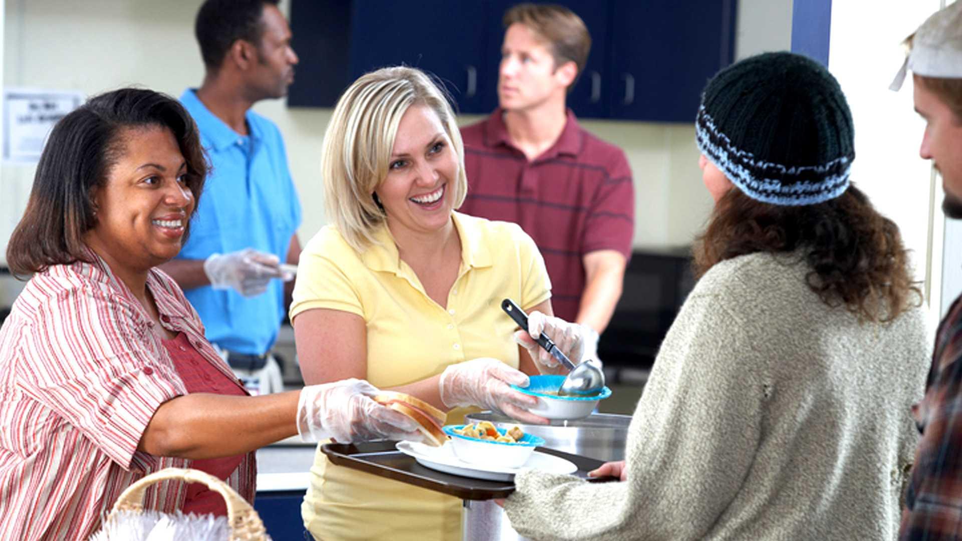 Volunteers serve food to those in need.