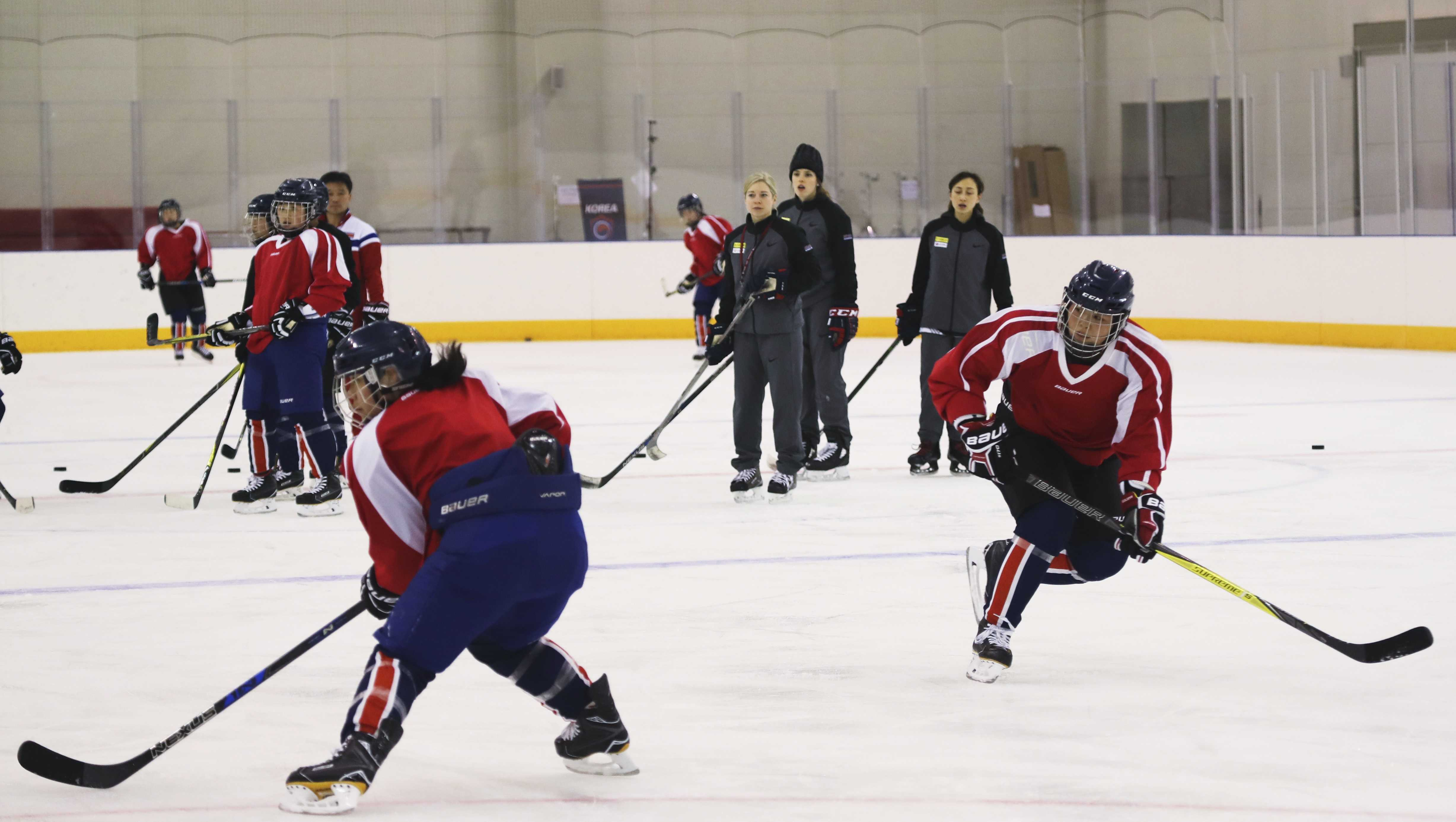 In this photo provided by South Korea Joint Government Support Corps, North Korean women's ice hockey players trains with South Korea women's hockey team head coach Sarah Murray, center, during the training at the South Korea's national training center in Jincheon, South Korea.