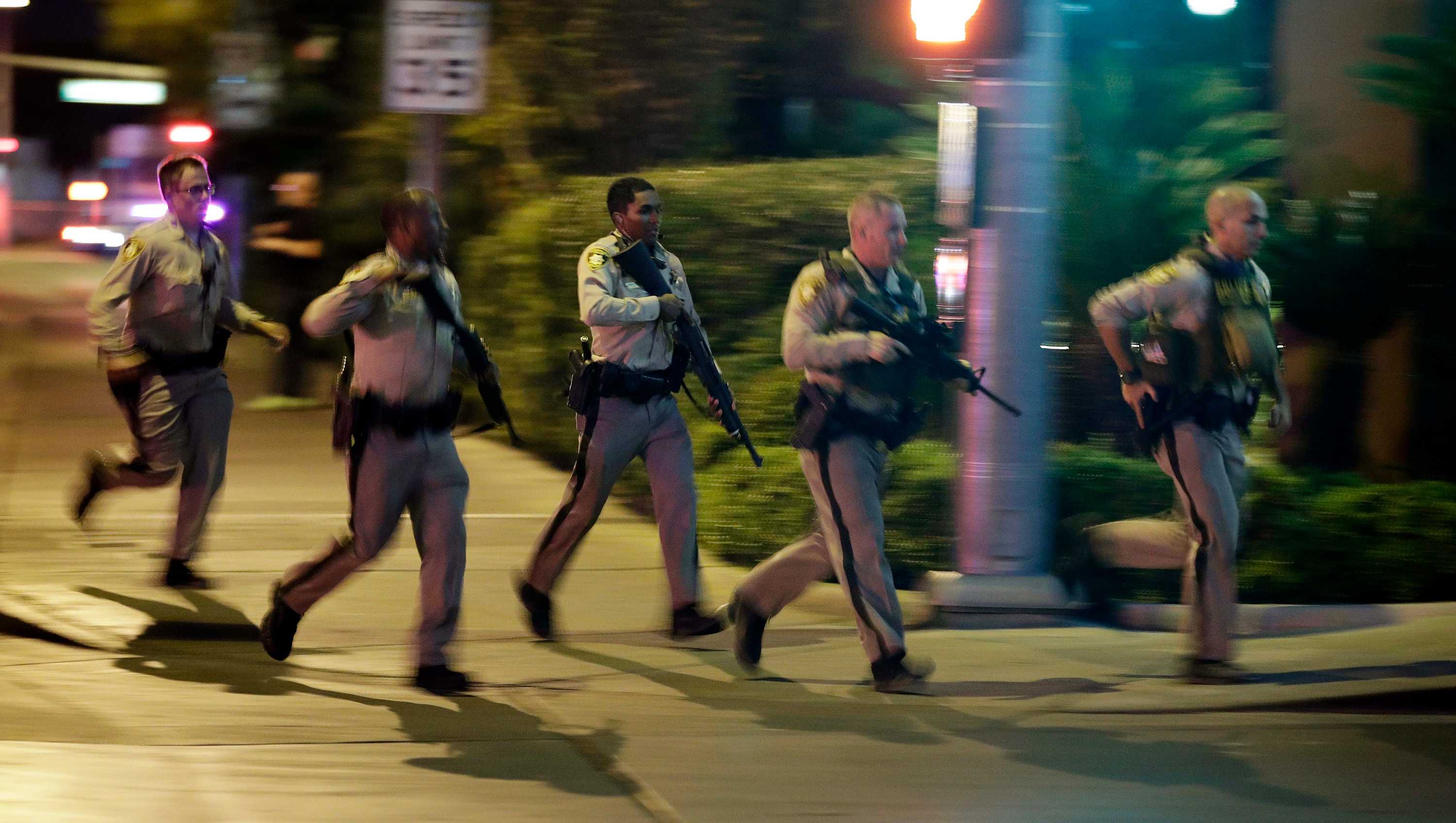 In this Sunday, Oct. 1, 2017, file photo, police run toward the scene of a shooting near the Mandalay Bay resort and casino on the Las Vegas Strip in Las Vegas.