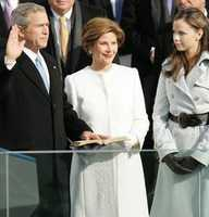 Laura Bush listens as Chief Justice William Rehnquist administers the oath on Jan. 20, 2005.