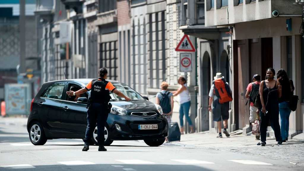 A police officer redirects a car in the eastern Belgian city of Liege on May 29, 2018, after an armed man shot and killed two police officers before being subdued by police. - 'There are two dead policemen and two others injured,' the spokeswoman for the Liege prosecutors office told AFP.