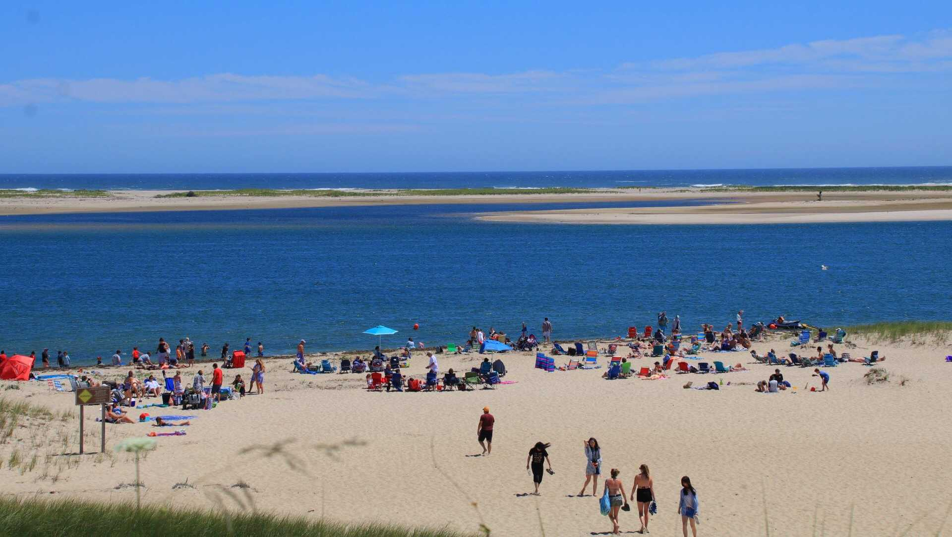 In this file image, beachgoers enjoy a sunny afternoon at Lighthouse Beach in Chatham, Mass.