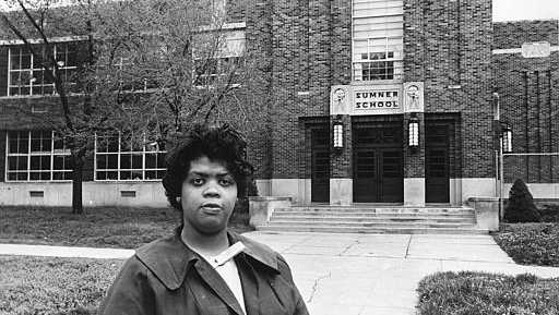 "Linda Brown Smith stands in front of the Sumner School in Topeka, Kansas, on May 8, 1964. The refusal of the public school to admit Brown in 1951, then nine years old, because she is black, led to the Brown v. Board of Education of Topeka, Kansas. In 1954, the U.S. Supreme Court overruled the ""separate but equal"" clause and mandated that schools nationwide must be desegregated."