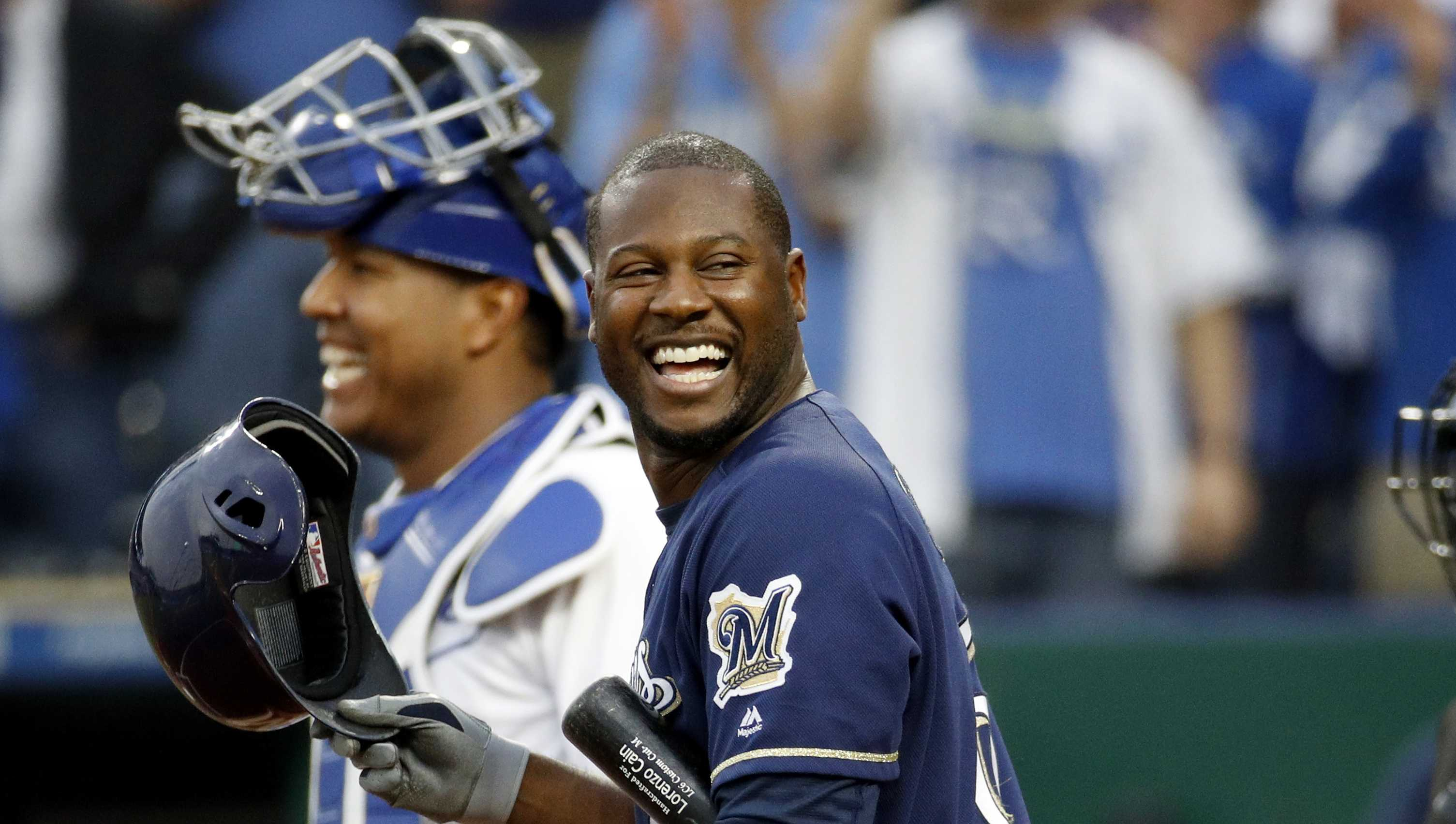 Milwaukee Brewers' Lorenzo Cain smiles at the crowd as they cheer the former Royal before his at bat during the first inning of a baseball game against the Kansas City Royals Tuesday, April 24, 2018, in Kansas City, Mo. (AP Photo/Charlie Riedel)
