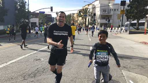 In this March 18, 2018, photo provided by Pash Pashkow, movie production lawyer Loren Zitomersky, left, runs the Los Angeles Marathon backward as a young runner briefly accompanies him.