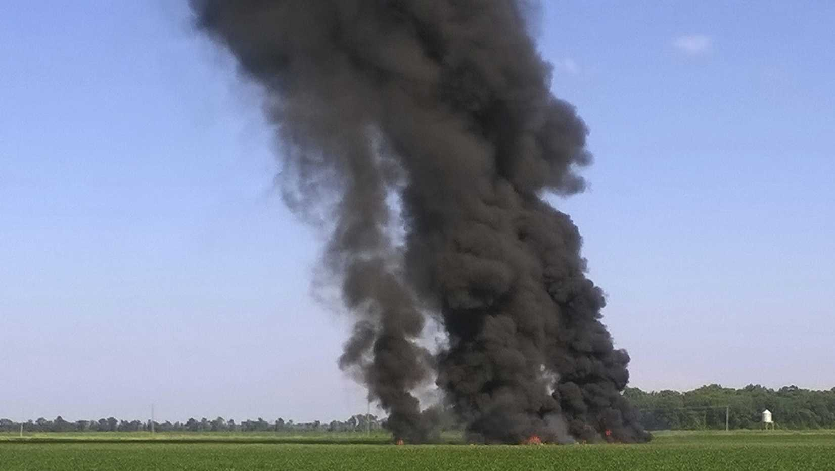 In this photo provided by Jimmy Taylor, smoke and flames rise into the air after a military transport airplane crashed in a field near Itta Bena, Miss., on the western edge of Leflore County, Monday, July 10, 2017, killing several.
