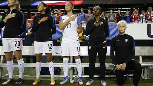 USA's Megan Rapinoe, right, kneels next to teammates Samanth Mewis (20) Christen Press (12), Ali Krieger (11), Crystal Dunn (16) and Ashlyn Harris (22) as the US national anthem is played before an exhibition soccer match against Netherlands Sunday, Sept. 18, 2016, in Atlanta.