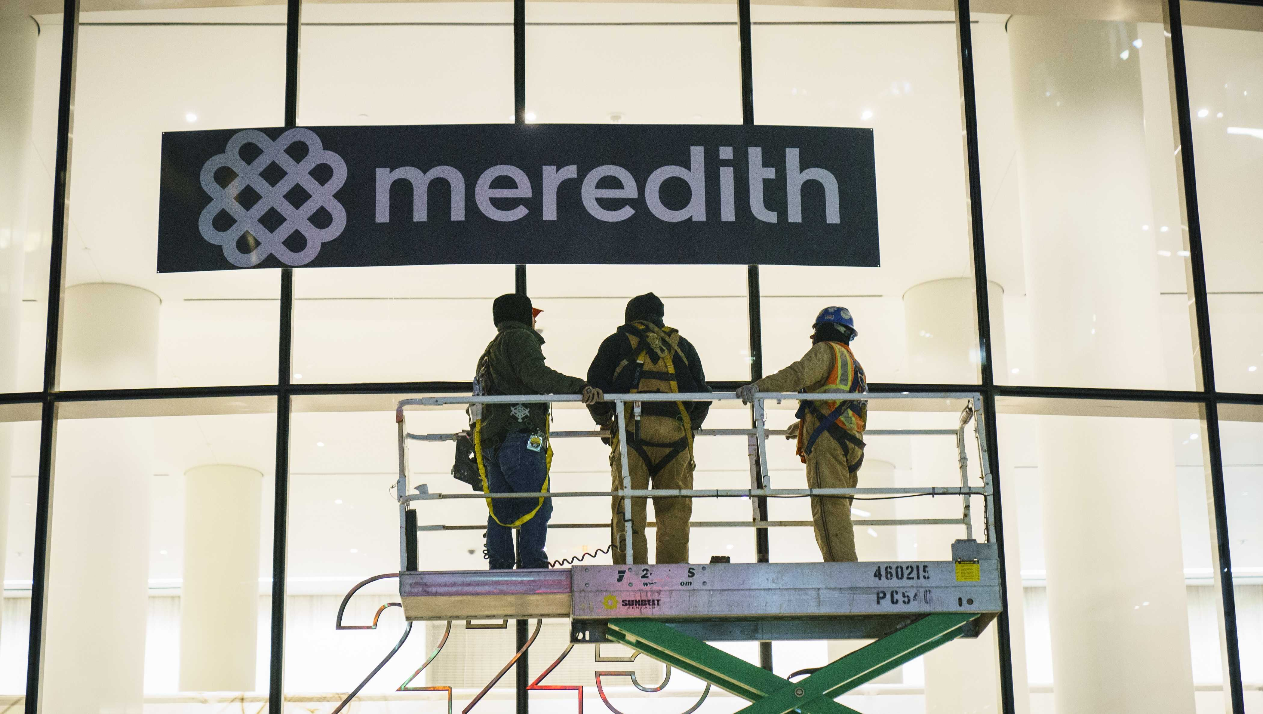 Workers cover up Time Inc. signage with Meredith Corporation signage at the Time Inc. office building in Lower Manhattan, January 31, 2018 in New York City.