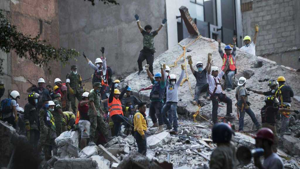 Rescuers raise hands for silence to listen for possible victims inside the rubble in Mexico City.