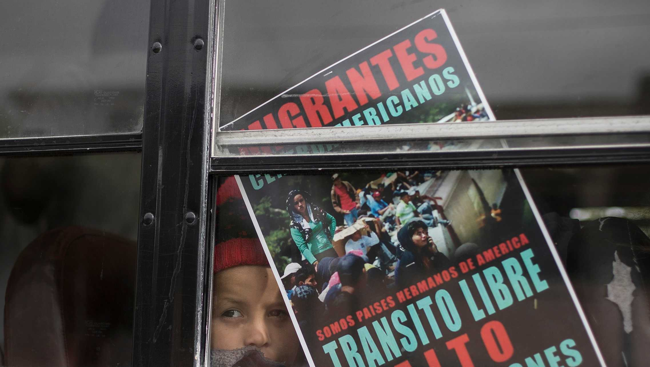 A Central American child who is traveling with a caravan of migrants, peers from a bus carrying the group to the border wall for a gathering of migrants living on both sides of the border, in Tijuana, Mexico, Sunday, April 29, 2018. The sign reads in Spanish: We're all brother countries from the Americas. Free transit. Stop the deportations.""