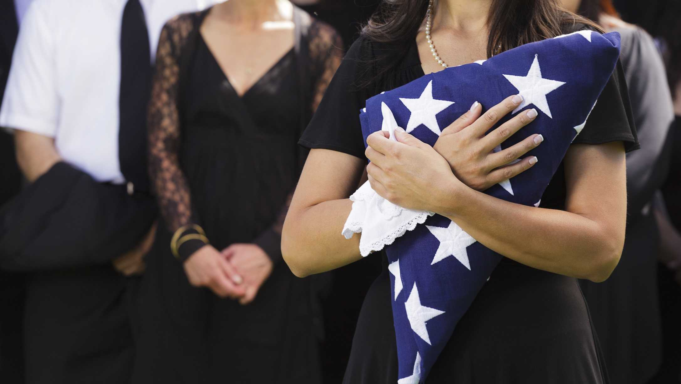 A woman holds a folded American flag at a funeral.