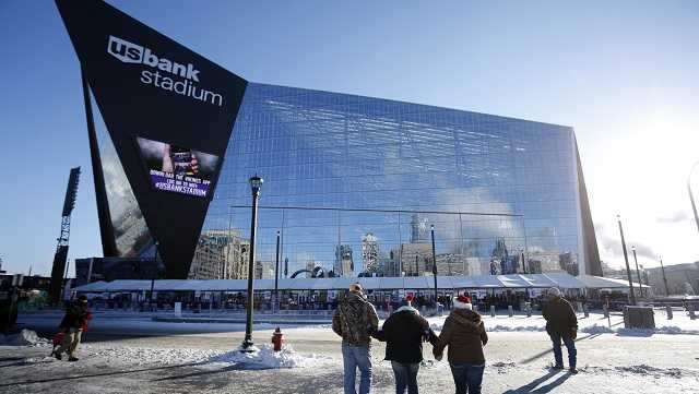 In this Dec. 18, 2016, file photo, fans bundled up for the cold weather head for U.S. Bank Stadium before the start of an NFL football game.