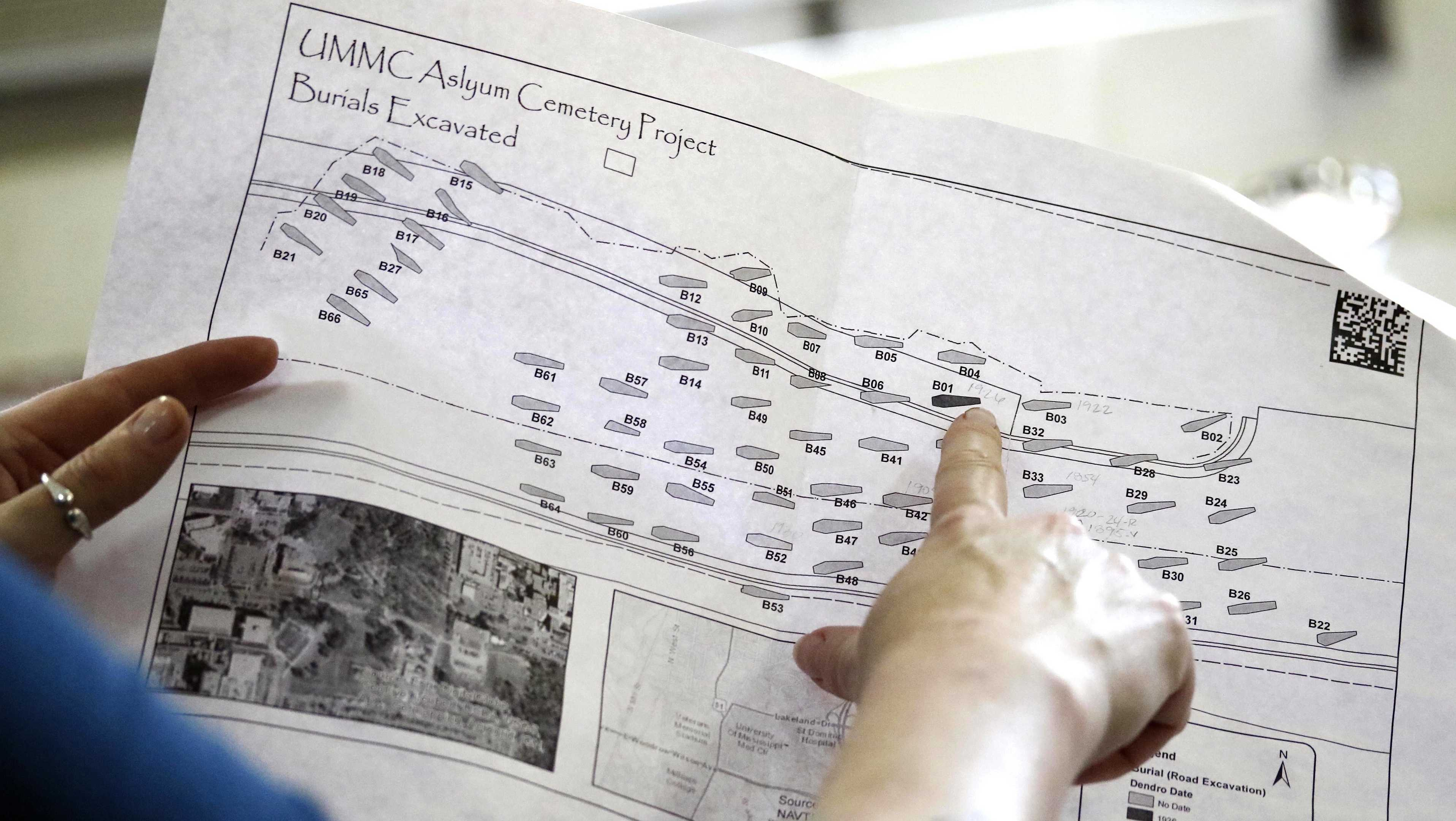 In this May 9, 2018 photo taken in Starkville, Miss., Mississippi State University anthropologist Anna Osterholtz holds a map outlining the 66 unearthed graves at what was the graveyard of the Mississippi State Asylum in Jackson, Miss.