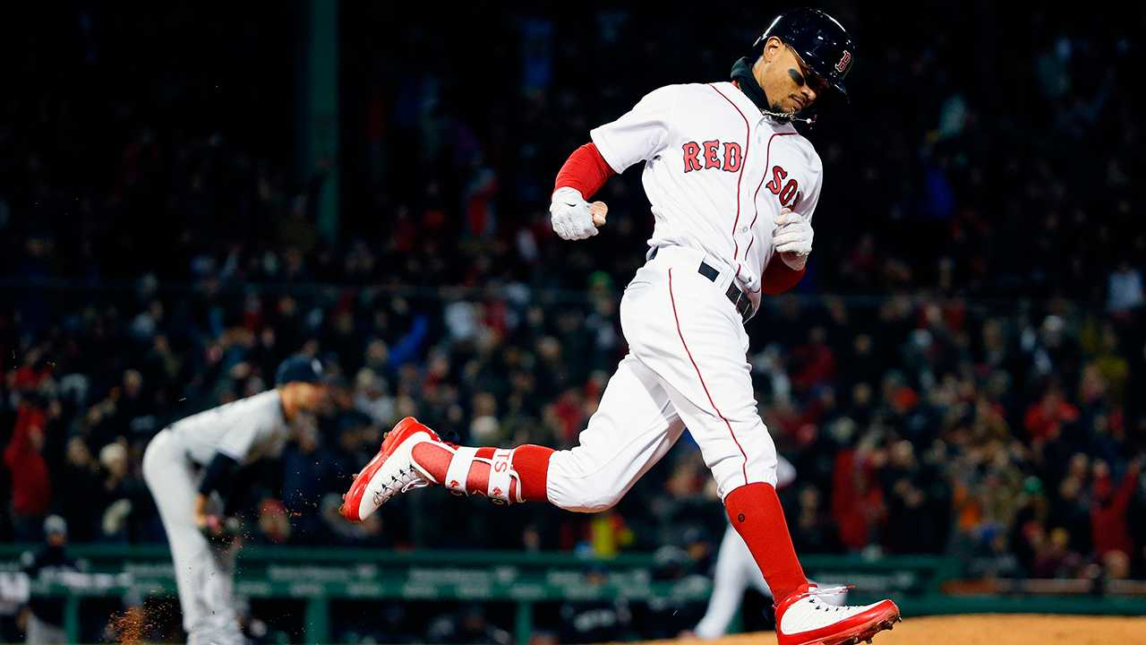 Boston Red Sox's Mookie Betts rounds first base on his grand slam off New York Yankees' Chasen Shreve, left, during the sixth inning of a baseball game in Boston, Tuesday, April 10, 2018.
