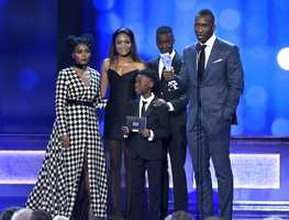 "Janelle Monae, from left, Naomie Harris, Ashton Sanders, Mahershala Ali, and from front center, Alex R. Hibbert, accept the award for best acting ensemble for ""Moonlight"" at the 22nd annual Critics' Choice Awards at the Barker Hangar on Sunday, Dec. 11, 2016, in Santa Monica, Calif."