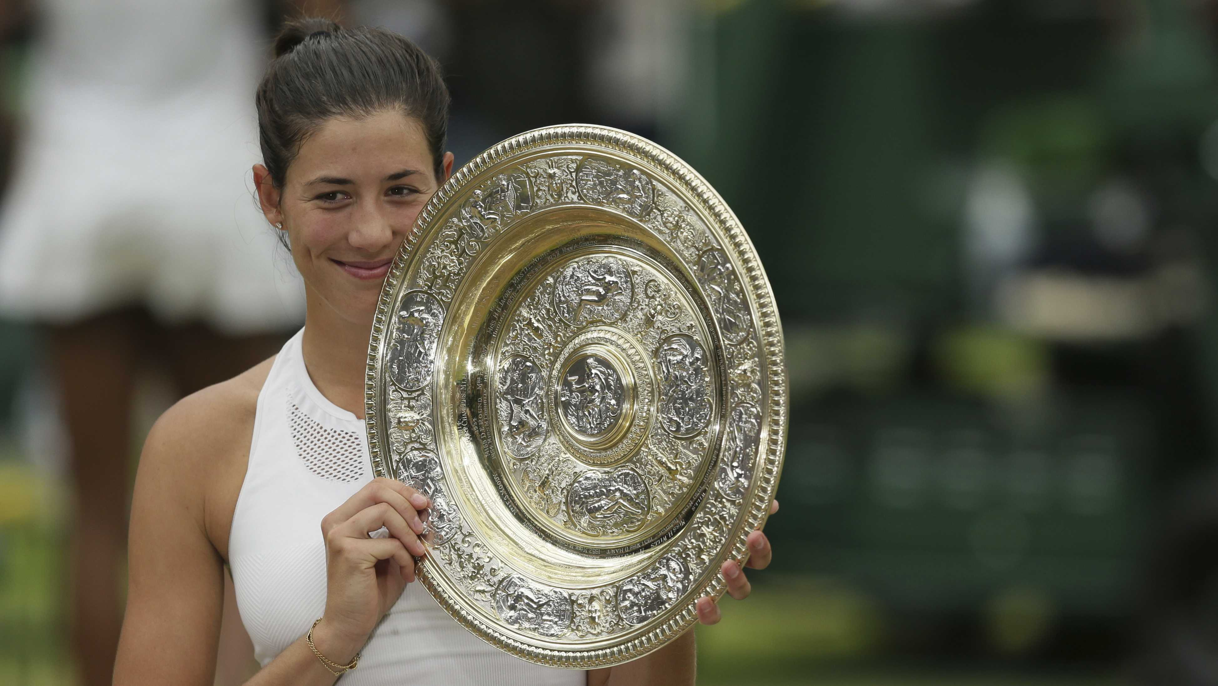 Spain's Garbine Muguruza holds up the trophy after defeating Venus Williams in the women's final at Wimbledon on July 15, 2017.