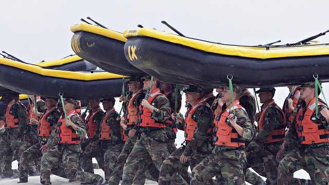In this May 14, 2009 file photo, Navy SEAL trainees carry inflatable boats at the Naval Amphibious Base Coronado in Coronado, Calif.