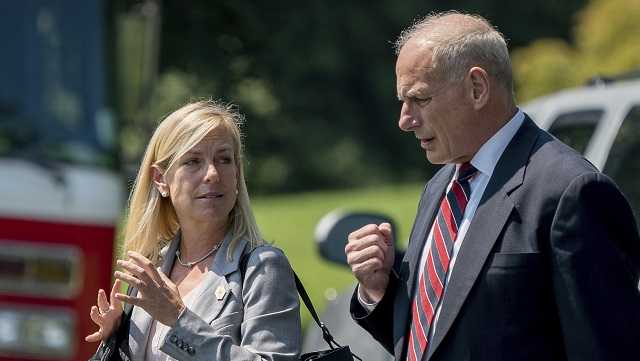 White House Chief of Staff John Kelly and Deputy Chief of Staff Kirstjen Nielsen speak together as they walk across the South Lawn of the White House in Washington, Tuesday, Aug. 22, 2017, to board Marine One with President Donald Trump for a short trip to Andrews Air Force Base, Md.
