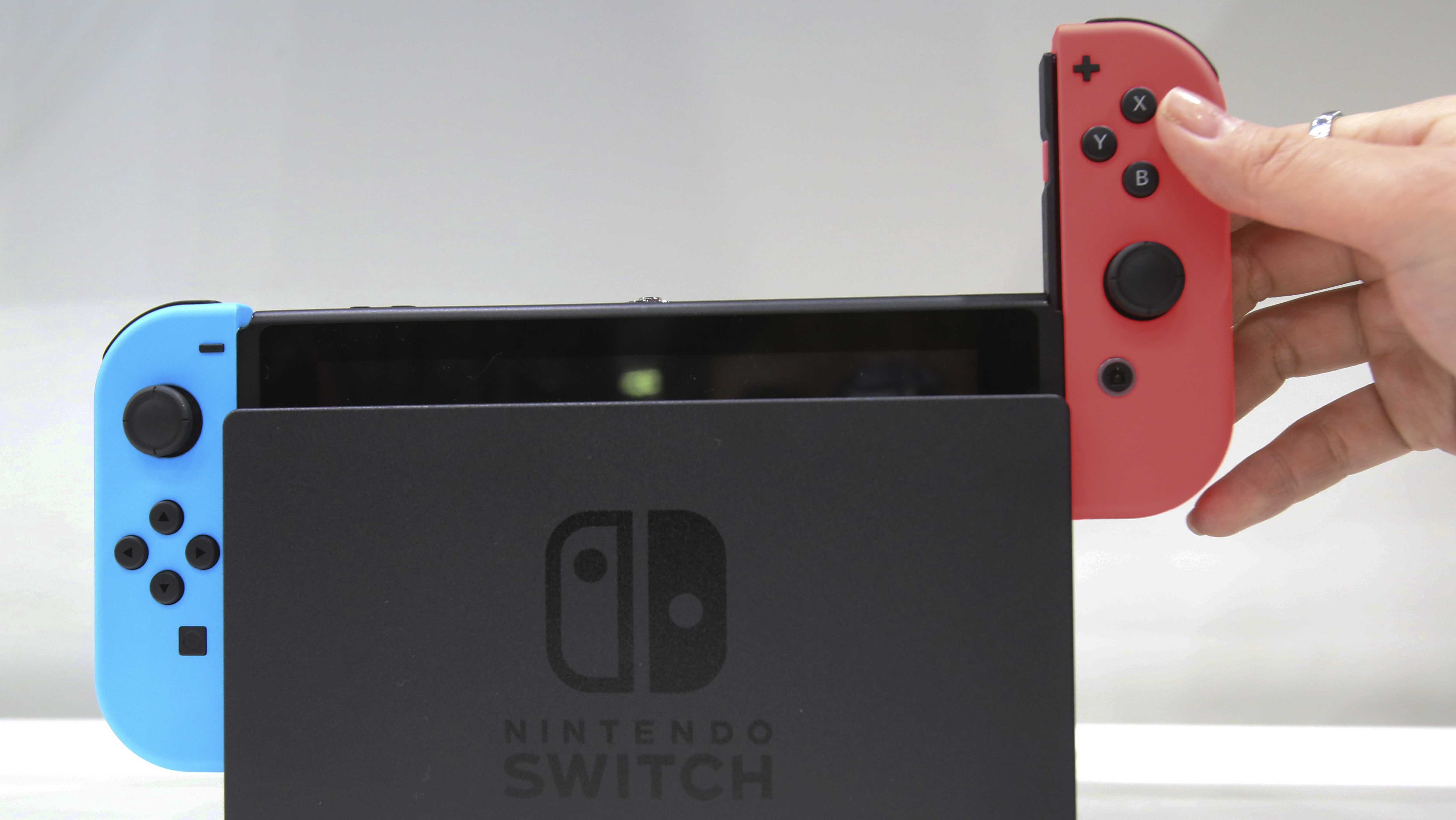 In this Friday, Jan. 13, 2017, file photo, a model puts the controller onto the Nintendo Switch during a presentation event of the new Nintendo Switch in Tokyo.