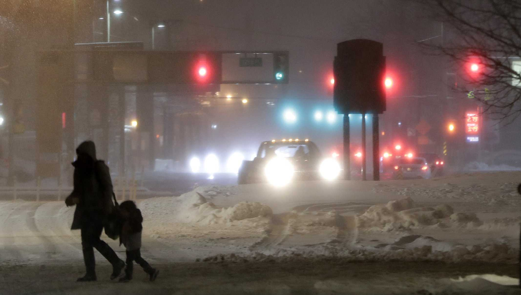 A woman and a child cross a snow-covered street during a snowstorm, Wednesday, March 21, 2018, in Jersey City, N.J. A spring nor'easter targeted the Northeast on Wednesday with strong winds and a foot or more of snow expected in some parts of the region.