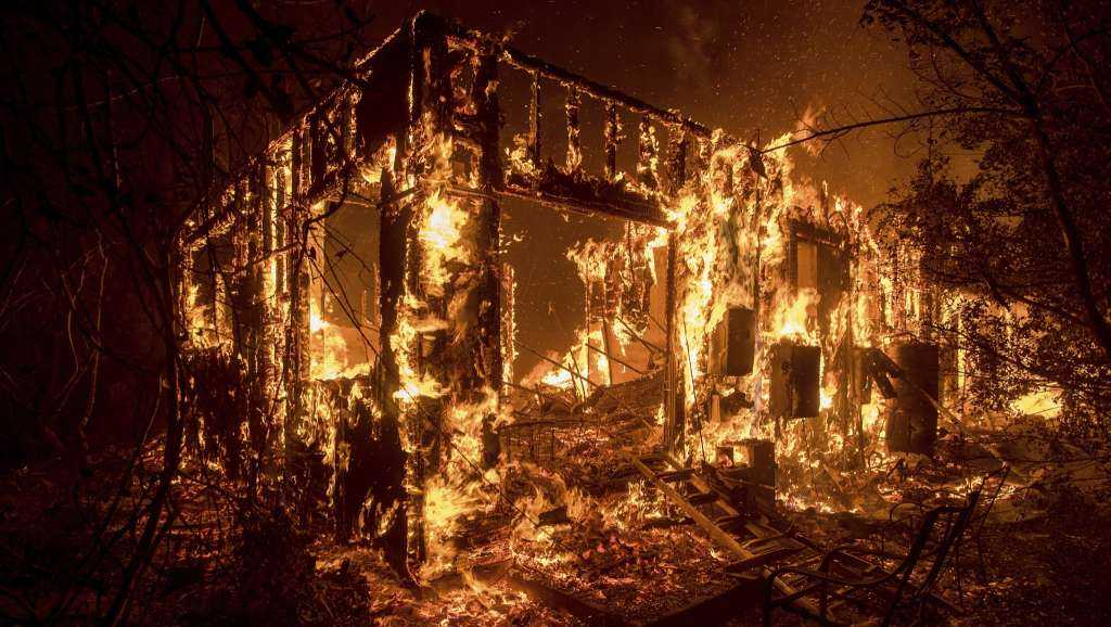 Flames consume a home as a wildfire burns in Ojai, Calif., on Dec. 7