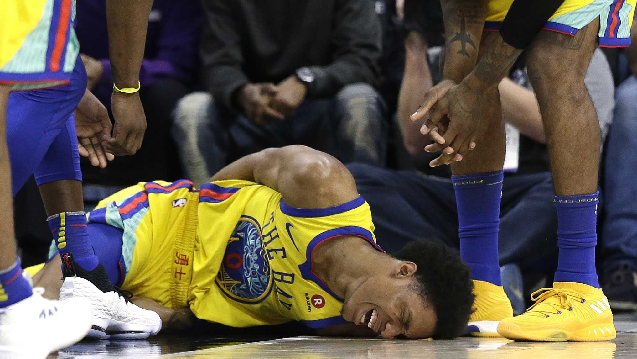 Golden State Warriors guard Patrick McCaw lays on the court in pain after falling hard to the floor late in the third quarter following a Flagrant 1 foul by Sacramento Kings's Vince Carter in an NBA basketball game Saturday, March 31, 2018, in Sacramento, Calif. McCaw was taken off the court on a stretcher.