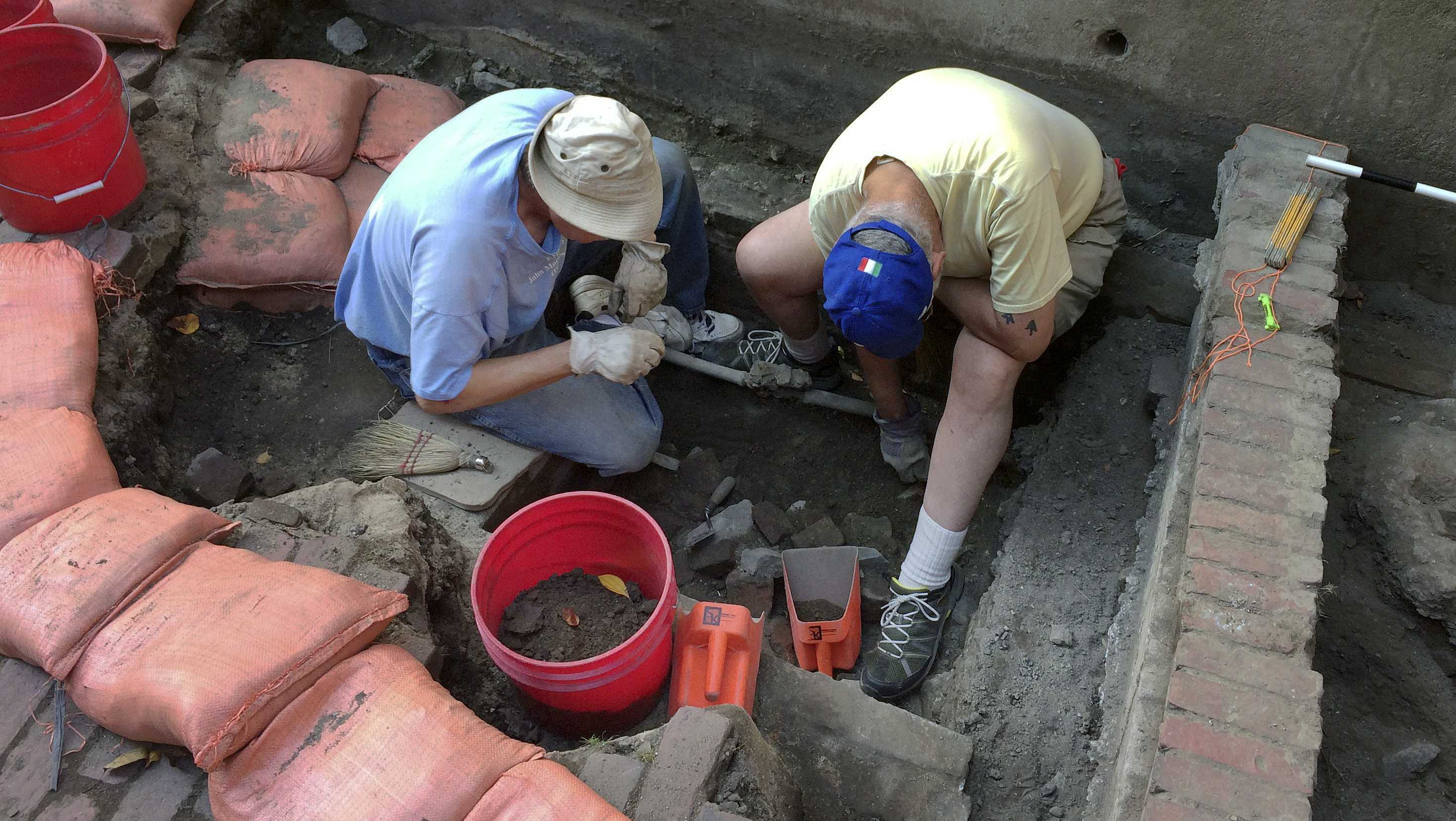 In this Sept. 28, 2017, photo, City of Boston Archaeological Program volunteers Tim Riordan, left, and Bob Sartini excavate a site that experts believe may have contained an outhouse used by Paul Revere. Fragments of pottery and a tobacco pipe already have been recovered from the dig outside the Pierce-Hichborn House in Boston's historic North End. Experts say the house, built next to Revere's house in 1711, was owned by one of Revere's cousins, and the renowned American patriot himself likely visited on numerous occasions.