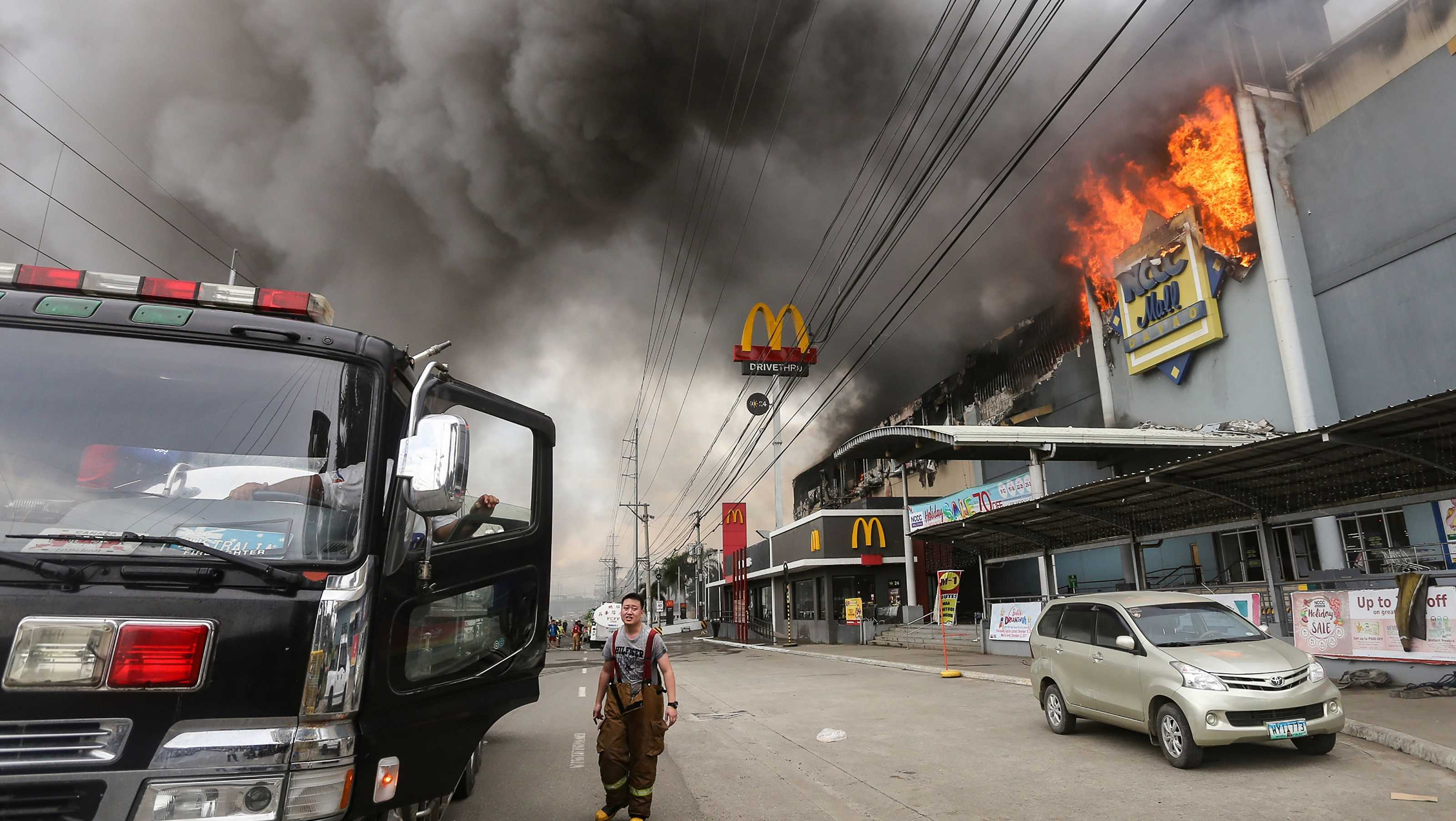 This photo shows a firefighter standing in front of a burning shopping mall in Davao City, on the southern Philippine island of Mindanao.