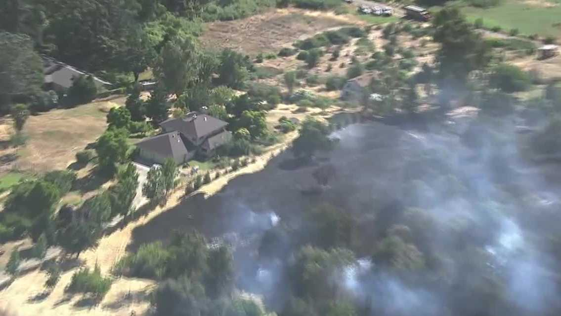 Crews contained a 3-acre grass fire Tuesday, June 13, 2017, before it spread to nearby homes.