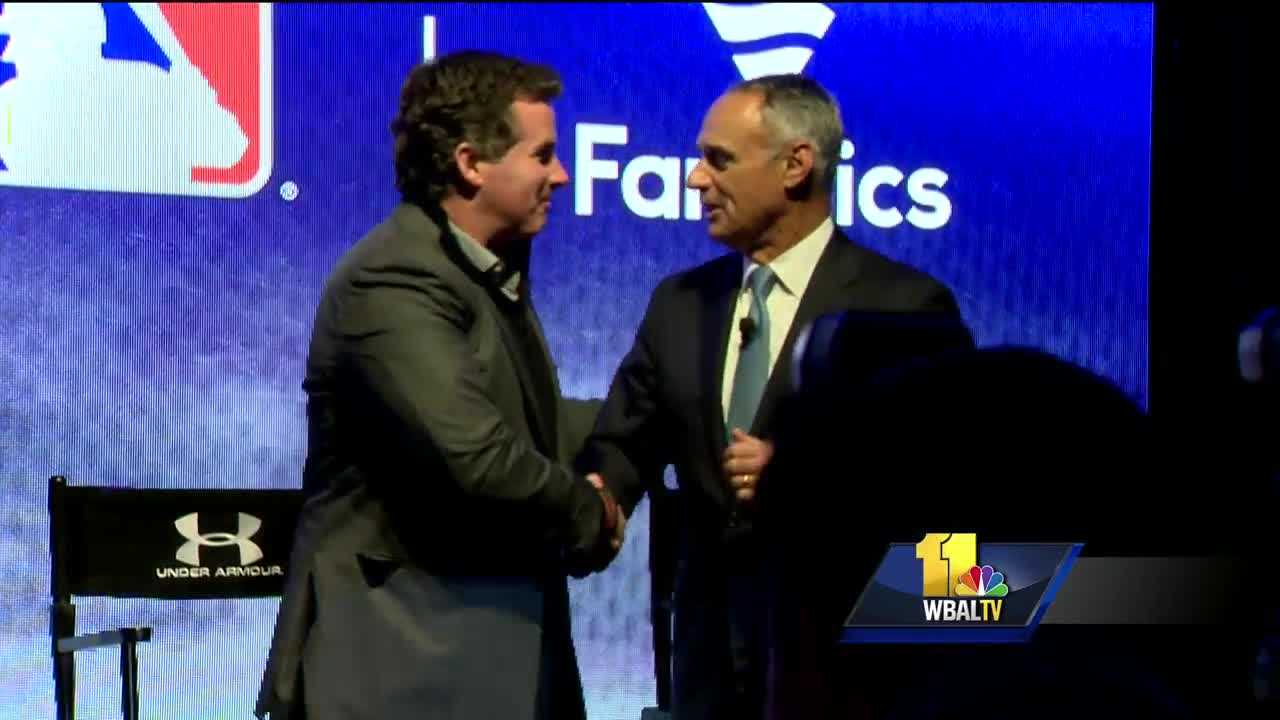 Under Armour founder and CEO Kevin Plank and MLB commissioner Rob Manfred shake hands after announcing a 10-year deal between their groups at baseball's winter meetings.
