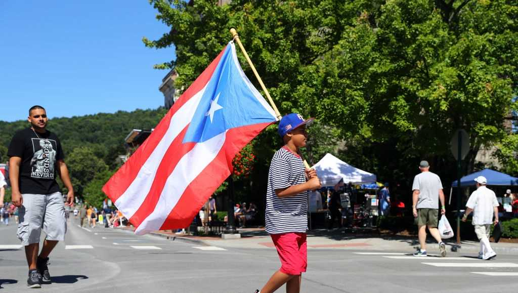 A young fan walks with a Puerto Rican flag down Main St. prior to the 2017 Hall of Fame Induction Ceremony at the National Baseball Hall of Fame on Sunday July 30, 2017 in Cooperstown, New York.