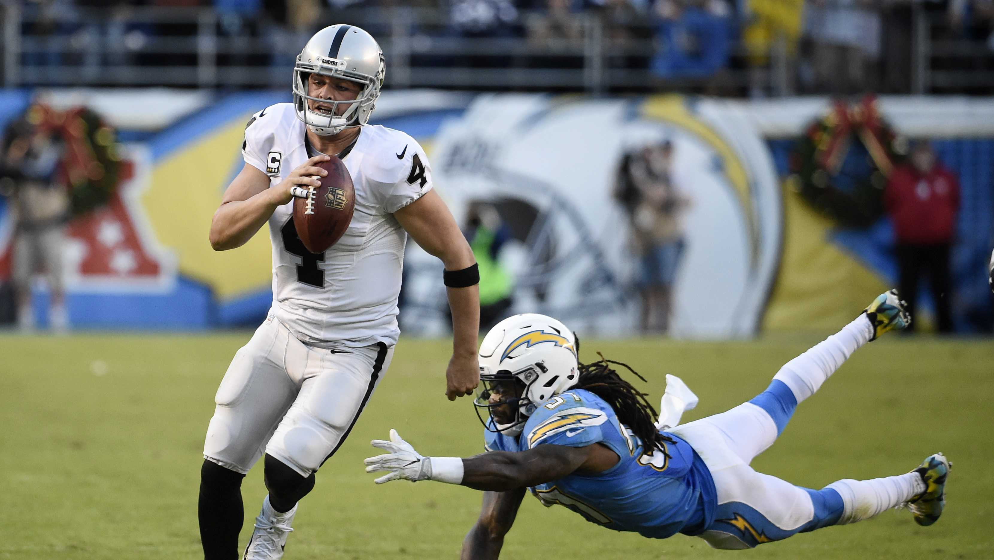 Oakland Raiders quarterback Derek Carr gets away from San Diego Chargers strong safety Jahleel Addae during the second half of an NFL football game Sunday, Dec. 18, 2016, in San Diego.